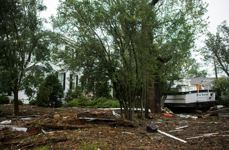A boat sits among debris in the front lawn of a house in New Bern, North Carolina