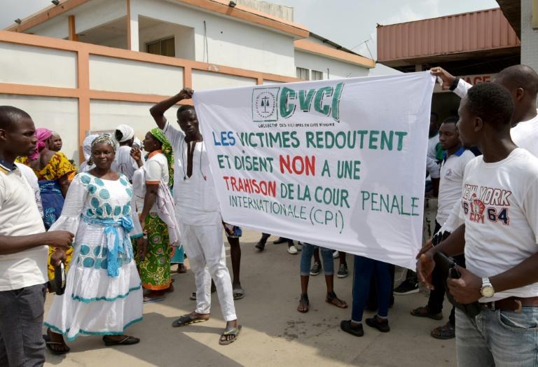 Demonstrators in Abidjan hold a banner reading
