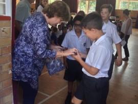 Parkview victim support member Debbi Burman hands out armbands at Parkview Senior Primary School.