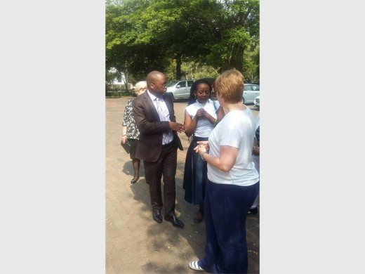 Minister of Justice and Correctional Services, Michael Masutha helps a parent enrol her child into Grade 1.