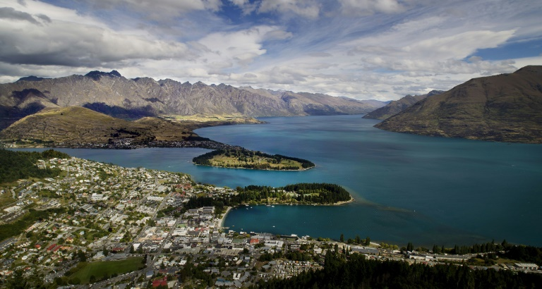 Views like this -- of Queenstown and Lake Wakatipu, with the Remarkables mountain range in the background -- are one of the reasons tourists flock to New Zealand. But strong economic growth is placing strains on the environment, the OECD is warning | © AFP/File | Marty MELVILLE