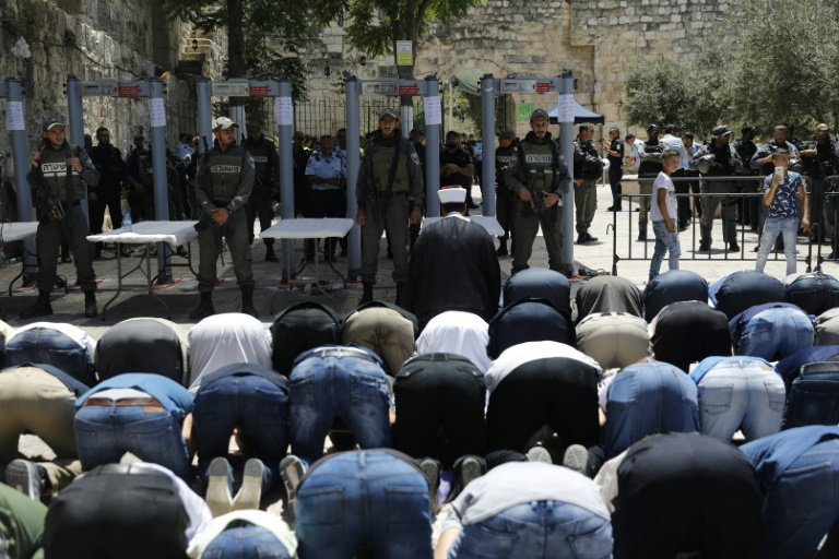 Israeli border policemen stand watch as Muslim worshippers pray outside an entrance to the Al-Aqsa mosque compound on July 16, 2017 in protest at new security measures including metal detectors and cameras | © AFP | Menahem KAHANA