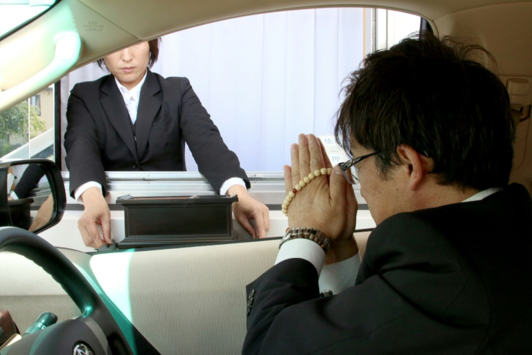 Drive-through mourners can register their names on a touchscreen tablet device and make a traditional offering of incense just by rolling down a car window | © Kankon Sosai Aichi Group/AFP | Handout
