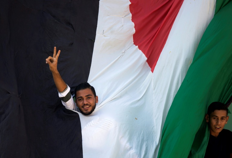 A Gazan flashes a victory sign behind a large Palestinian flag as he and others await the arrival of prime minister Rami Hamdallah on a visit that has raised hopes of an end to a decade-long split | © AFP | MOHAMMED ABED