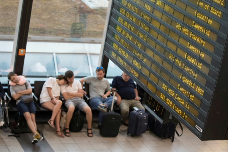 Passengers sleeping under a board listing all the cancelled Ryanair flights at Berlin's Schoenefeld Airport as the airline's pilots begin a 24-hour strike across Europe | © AFP | Odd ANDERSEN