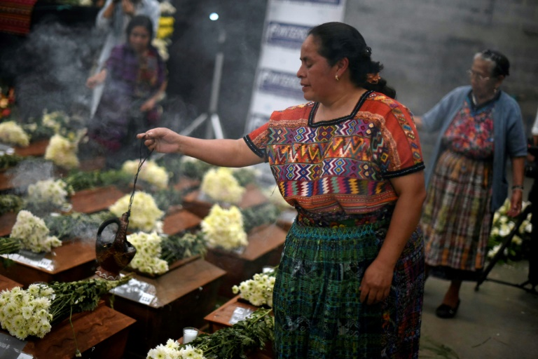 Indigenous women burn incense over urns with the remains of victims from Guatemala's 1960-1996 civil war after they arrived in San Juan Comalapa, Chimaltenango department, west of Guatemala City | © AFP/File | Johan ORDONEZ