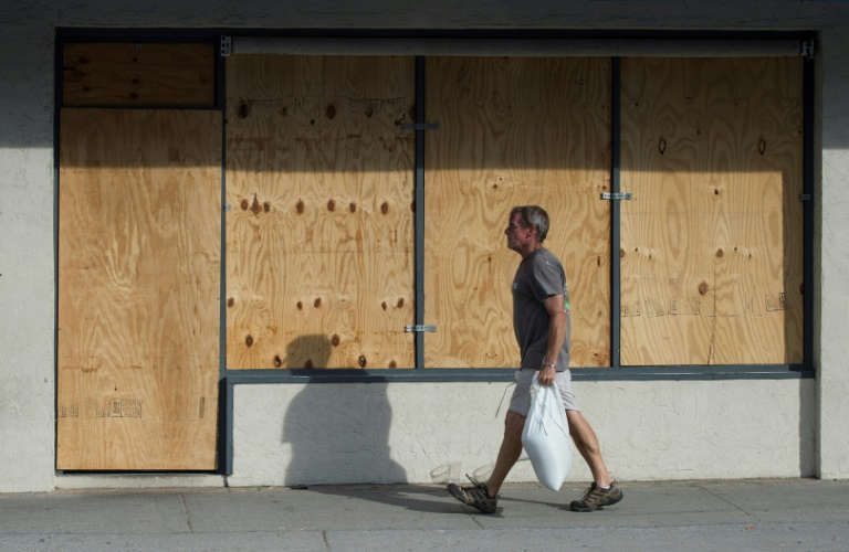 A man carries sandbags past a boarded up shop days before the arrival of hurricane Florence at Wrightsville Beach, North Carolina | © AFP | ANDREW CABALLERO-REYNOLDS