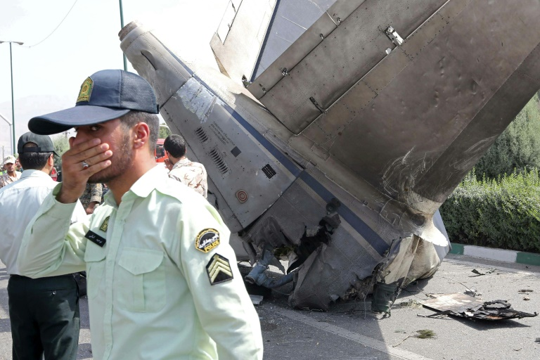 Iranian security forces stand at the scene of a previous plane crash near Tehran's Mehrabad airport on August 10, 2014   © AFP   ATTA KENARE