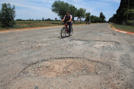 A cyclist rides past one of the huge potholes at the intersection of Lang and Andries streets.
