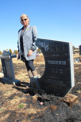 Me. Annett Venter by een van die grafte wat in die brand beskadig is.