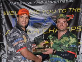 Meyer du Plessis (regs) ontvang sy trofee as wenner van Danie van Huyssteen, 'n direkteur van SADPA South African Defensive Pistol Association (SADPA).