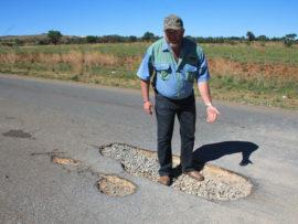 Mr Ben van den Berg shows the deep hole at which a motorist damaged his vehicle last week.