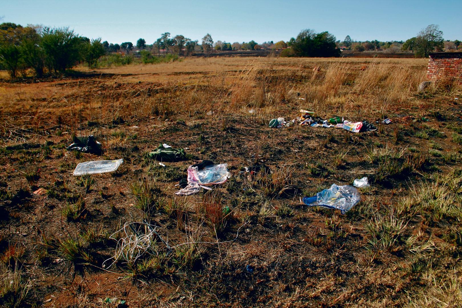 Van die aaklige gemors het steeds die week in die half uitgebrande veld gelê.