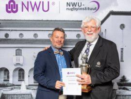 Dr. Pieter van der Berg (links) ontvang sy toekenning as die NWU Rugbyinstituut se Afrigter van die Jaar vir 2018. Langs hom staan die adjunk visie-kanselier van die NWU, prof. Fika Janse van Rensburg