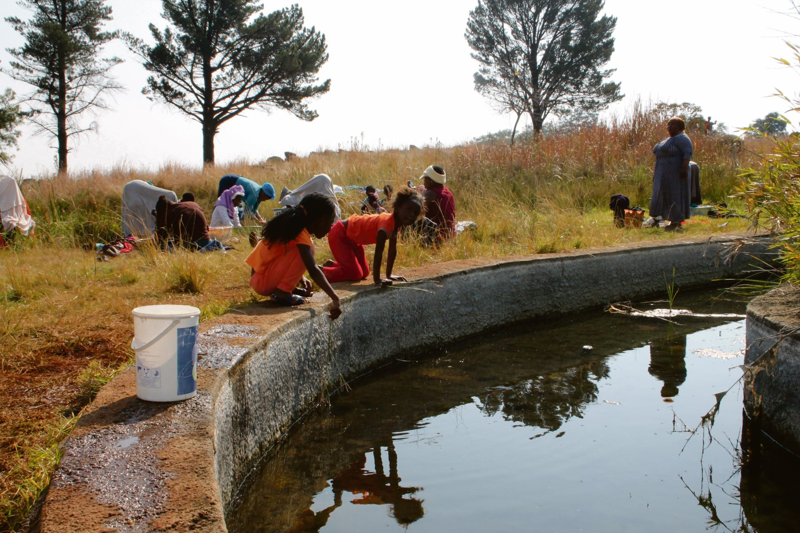 Children and women at the polluted pond that was not only used for drinking water, but also for washing clothes in Blyvoor during the past week.