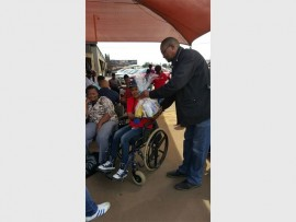 Eric Xayiya, the advisor of the Gauteng premier, handing out food parcels on behalf of Wheels of Change. On the wheelchair and receiving the parcel is Basetsana Masekoa, who participated in the race on the day.