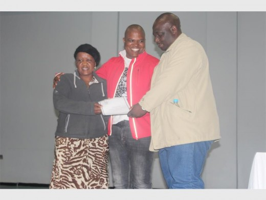MMC of housing Lesiba Mpya (middle) handing over the title deed to the couple Naville (left) and Dumisane Luvuno (right).
