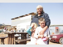 Irene van Niekerk with a Pango Camp family's two children, Kiana (4) and her brother Renier (7) Bezuidenhout, that she sees as her own family.