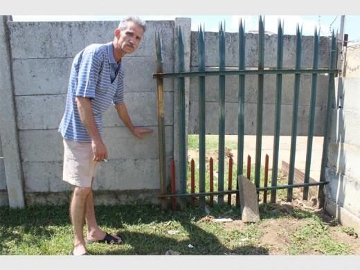 Hennie Coetzee dui aan hoe hoog die water opgestoot het voordat die betonmuur ingegee het en die water deurgelaat het. Die gesin het nou tydelike pelisade teen die muur opgesit.