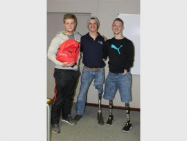Students Lance McGill (left) and Zane Bauermeister (right) handing over their donation to Jumping Kids manager Michael Stevens (middle).