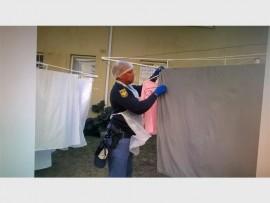 'n Polisielid help met wasgoed op Mandela-dag by Môreglans Tehuis. Foto verskaf.