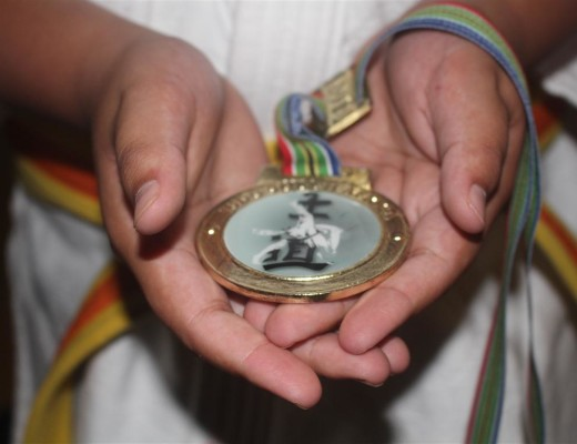 A judoka of KJK holds the gold medal he won at the South African Primary Schools Judo Tournament.