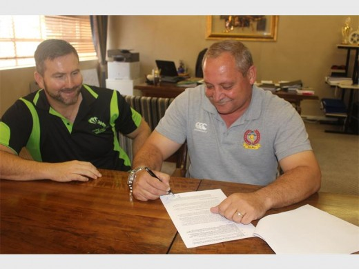 Peer Assor, lid van Jump Stretch en Teuns Naudé, voorsitter van Hoërskool Bastion se beheerliggaam teken 'n kontrak om die nuwe strekband-gimnasium te finaliseer.