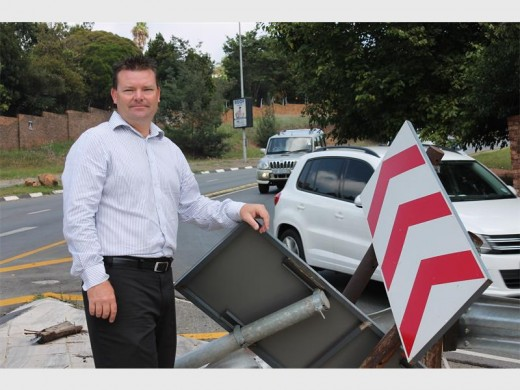 Ward 85 councillor Carl Mann shows the damage done to the embankment and barriers on Christiaan de Wet and Wilgerood Roads in a recent accident. Behind him, motorists take the slipway from Wilgerood into Christiaan de Wet Road. Photo: Mathilde Myburgh.