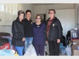 Anette van Rensburg, Griet van Zyl, Alta Weare en Mari de Lange staan tussen die skenkings wat die gemeenskap gedoen het. (Foto: Riaan van Zyl)