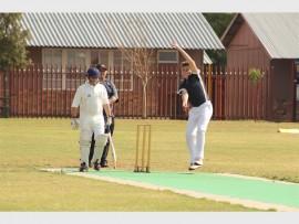 Laerskool Helderkruin's bowler Divan Swart during his delivery stride asLaerskool Horison batsman Gustav Jansen van Rensburg watches on.