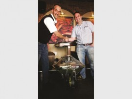 Dros manager, Brett Goad (left), congratulates Jason Mansfield on winning the wheelbarrow raffle.
