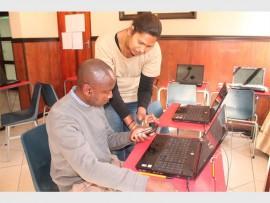 Kashnie Padayachee assisting parent Nathania Nel during his online registration at Boksburg High School.