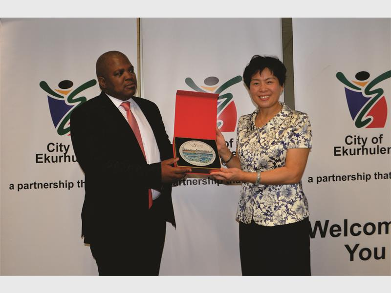 City of Ekurhuleni's MMC of Human Settlement, Cllr Lesiba Mpya, with the People's Government of Sammenxia's (China) deputy mayor, Mrs Li Qinghong, holding a token of appreciation during a meeting, that will prospectively establish a productive trade and academia partnership between both municipalities.
