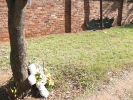 Geliefdes van Jaco Boshoff het, na die ongeluk wat sy lewe geëis het, blomme teen 'n boom gaan plaas. Op die agtergrond kan 'n wrakstuk van een van die voertuie, wat gister in die botsing was, gesien word.