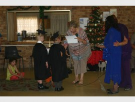 Marietjie Goller wens twee van die kleintjies, wat volgende jaar skool toe gaan, geluk.