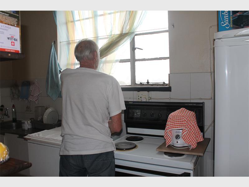 Die 71-jarige man staan hier by die kombuisvenster, waar die inbreker betrap is.
