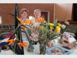 Delores van Rooyen (links) en die voorsitter van die Brakpan VLU, Hettie Basson, staan hier by sommige van die blommerangskikkings wat deur lede van die tak geskep is. Die rangskikkings is tydens die onlangse maandvergadering  van die tak behoordeel.