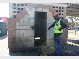 Zinhle (27) points to the leaking taps inside the graffiti-covered toilet building