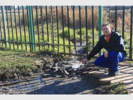Anthony Pretorius (48) points at the sewage that streams into the veld situated across from the premises from where he operates his business.