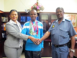 Cst George Mpati (34) (middle) receives handshakes from Col Thandi Thwala (left) Springs police detective branch commander and Col Doctor Mthinthulu, the Visible Police head. George received seven silver medals for half-marathons he finished this year.