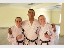 Samantha Maré, Kruben Pillay (karate-instrukteur) en Laikin Barnard met hulle kanji's.