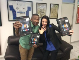 Daniel Seleme (Caxton East Rand project leader) and Brigitte Thysse (regional public relations officer for Hirsch's Home-Stores) show off the Kindles that are up for grabs in this year's spelling bee.