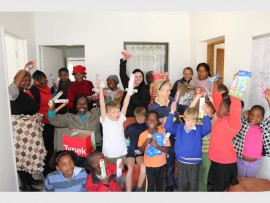Brigitte Thysse, regional public relations and marketing manager for Hirsch's Johannesburg (centre, back) has some fun with the children and staff from Epworth Children's Village.