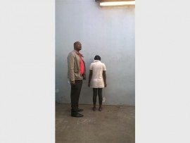 Det-WO France Magoro (left) stands guard over a 21-year-old woman who was recently arrested by the Primrose police, on charges of child neglect.
