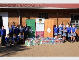 Chris Kruger (principal of Laerskool Oosterkruin, right), Loma du Preez (chairman of PRAC), Pieter Greyling (left), Wico Swanepoel (provincial co-ordinator for AfriForum) and several Laerskool Oosterkruin students show how much water the school managed to collect to donate to the people of Senekal, in the Free State.