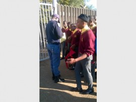 A Katlehong police officer searches several Mpontseng Secondary School students as part of the station's recent school visit.