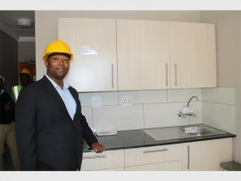 """The head of department for human settlements, Bongani Molefe, in the kitchen of the """"show"""" unit, in Delville Extension Nine, which now needs a few decisions from the municipality before the rest of the units can be completed."""