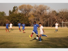 Germiston City Football Club's Dembi Mayimela (left, blue) unleashes his defence skills on his Olympia Football Club opponent during their fixture at the Germiston City Sports Club on Saturday.