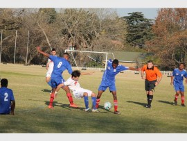 Germiston City FC's Alex Njosa (right, blue) effectively tackles his Olympia FC opponent. For more photos and a video visit www.germistoncitynews.co.za