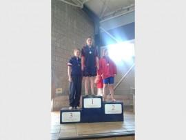 Here Nikita Coetzer (centre) receives her gold medal.